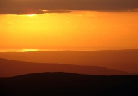 Layered hills lead the eye from the slopes of Fan Brycheiniog to the setting sun over a distant Swansea Bay